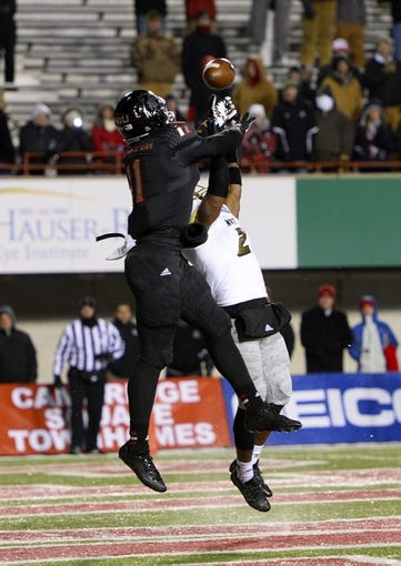 Nov 26, 2013; DeKalb, IL, USA; Northern Illinois Huskies wide receiver Juwan Brescacin (11) attempts to make a catch against Western Michigan Broncos safety Demetrius Pettway (2) during the fourth quarter at Huskie Stadium. NIU defeats Western Michigan 33-14. Mandatory Credit: Mike DiNovo-USA TODAY Sports