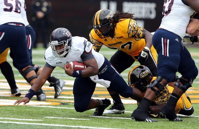 Nov 16, 2013; Hattiesburg, MS, USA; Florida Atlantic Owls quarterback Jaquez Johnson (12) dives for yards while tackled by Southern Mississippi Golden Eagles defensive lineman Octavius Thomas (99) during the first half at M.M. Roberts Stadium. Mandatory Credit: Chuck Cook-USA TODAY Sports