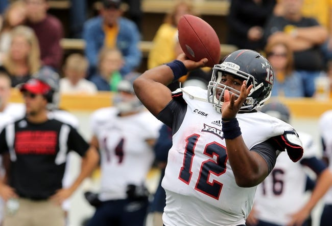 Nov 16, 2013; Hattiesburg, MS, USA; Florida Atlantic Owls quarterback Jaquez Johnson (12) makes a throw against the Southern Mississippi Golden Eagles during the first half at M.M. Roberts Stadium. Mandatory Credit: Chuck Cook-USA TODAY Sports