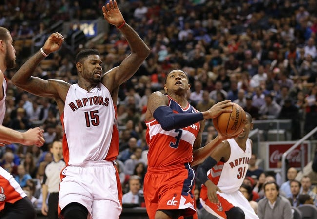 Nov 22, 2013; Toronto, Ontario, CAN; Washington Wizards shooting guard Bradley Beal (3) goes to the basket against Toronto Raptors forward Amir Johnson (15) at Air Canada Centre. The Raptors beat the Wizards 96-88. Mandatory Credit: Tom Szczerbowski-USA TODAY Sports
