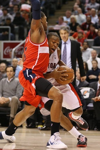 Nov 22, 2013; Toronto, Ontario, CAN; Toronto Raptors point guard Kyle Lowry (7) runs into Washington Wizards shooting guard Bradley Beal (3) as he goes to the basket  at Air Canada Centre. The Raptors beat the Wizards 96-88. Mandatory Credit: Tom Szczerbowski-USA TODAY Sports