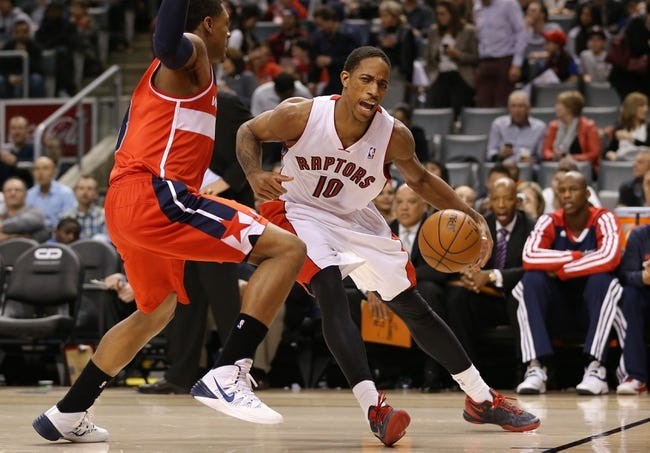 Nov 22, 2013; Toronto, Ontario, CAN; Toronto Raptors guard DeMar DeRozan (10) tries to get past Washington Wizards shooting guard Bradley Beal (3) at Air Canada Centre. The Raptors beat the Wizards 96-88. Mandatory Credit: Tom Szczerbowski-USA TODAY Sports