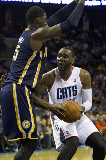 Nov 27, 2013; Charlotte, NC, USA; Charlotte Bobcats center Al Jefferson (right) goes in for the layup while being defended by Indiana Pacers center Roy Hibbert (left) during the second quarter at Time Warner Cable Arena. Mandatory Credit: Joshua S. Kelly-USA TODAY Sports
