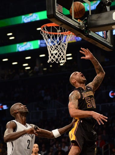 Nov 27, 2013; Brooklyn, NY, USA; Los Angeles Lakers center Robert Sacre (50) puts up a layup past the defense of Brooklyn Nets power forward Kevin Garnett (2) during the first half at Barclays Center. The Lakers won 99-94. Mandatory Credit: Joe Camporeale-USA TODAY Sports