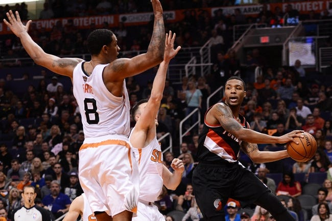 Nov 27, 2013; Phoenix, AZ, USA; Portland Trail Blazers guard Damian Lillard (0) passes the ball around Phoenix Suns forward Channing Frye (8) in the first half at US Airways Center. The Suns won 120-106.  Mandatory Credit: Jennifer Stewart-USA TODAY Sports
