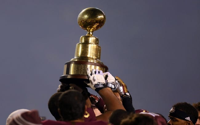 Nov 28, 2013; Starkville, MS, USA; Mississippi State Bulldogs players hold up the egg bowl trophy after winning the game against the Mississippi Rebels at Davis Wade Stadium. Mississippi State Bulldogs defeat the Mississippi Rebels with a score of 17-10 in overtime.  Mandatory Credit: Spruce Derden-USA TODAY Sports