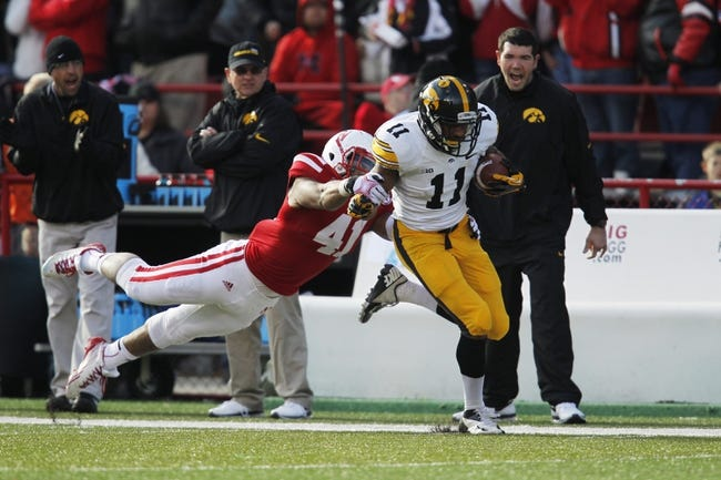 Nov 29, 2013; Lincoln, NE, USA; Iowa Hawkeyes receiver Kevonte Martin-Manley (11) catches the pass and is tackled by Nebraska Cornhuskers defender David Santos (41) in the third quarter at Memorial Stadium. Mandatory Credit: Bruce Thorson-USA TODAY Sports
