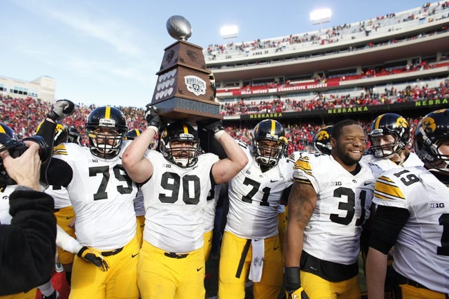 Nov 29, 2013; Lincoln, NE, USA; Iowa Hawkeyes defensive lineman Louis Trinca-Pasat (90) carries the Heroes Game trophy after defeating the Nebraska Cornhuskers at Memorial Stadium. Iowa won 38-17. Mandatory Credit: Bruce Thorson-USA TODAY Sports