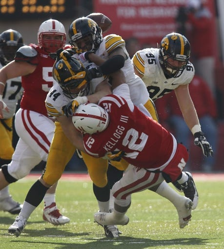 Nov 29, 2013; Lincoln, NE, USA; Nebraska Cornhuskers quarterback Ron Kellogg III (12) is tackled by Iowa Hawkeyes defenders James Morris (44) and Nico Law (21) in the third quarter at Memorial Stadium. Iowa won 38-17. Mandatory Credit: Bruce Thorson-USA TODAY Sports