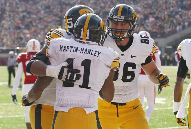 Nov 29, 2013; Lincoln, NE, USA; Iowa Hawkeyes receiver Kevonte Martin-Manley (41) scores a touchdown and is congratulated by lineman Jordan Walsh (65) and tight end C.J. Fiedorowicz (86) during game against Nebraska Cornhuskers in the third quarter at Memorial Stadium. Iowa won 38-17. Mandatory Credit: Bruce Thorson-USA TODAY Sports