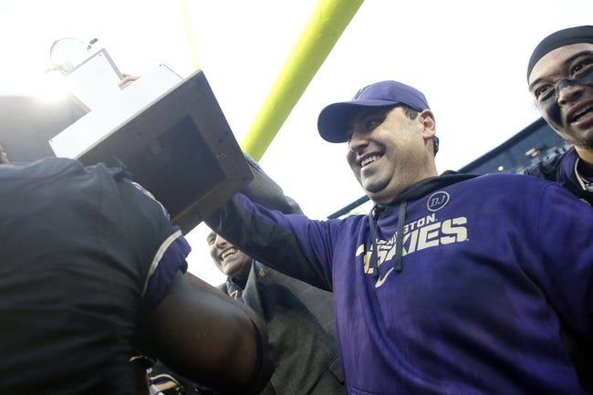 Nov 29, 2013; Seattle, WA, USA; Washington Huskies head coach Steve Sarkisian lifts up the Apple Cup trophy with Governor Jay Inslee following a 27-17 Washington victory against the Washington State Cougars at Husky Stadium. Mandatory Credit: Joe Nicholson-USA TODAY Sports
