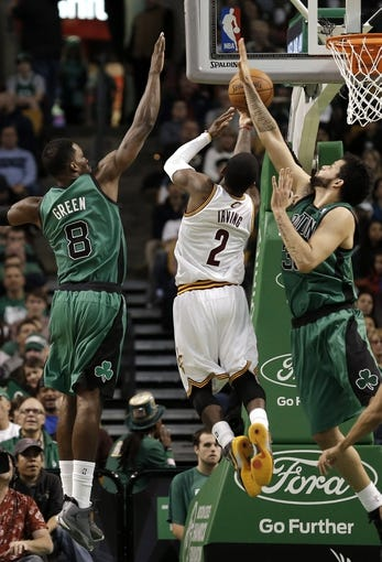 Nov 29, 2013; Boston, MA, USA; Cleveland Cavaliers point guard Kyrie Irving (2) drives between Boston Celtics shooting guard Jeff Green (8) and center Vitor Faverani (38) during the second quarter at TD Garden. Mandatory Credit: Winslow Townson-USA TODAY Sports