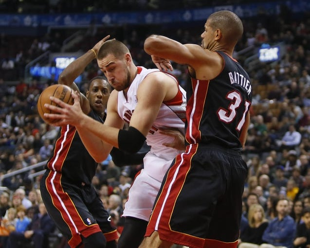 Nov 29, 2013; Toronto, Ontario, CAN; Toronto Raptors center Jonas Valanciunas (17) tries to battle through Miami Heat guard Mario Chalmers (15) and Miami Heat forward Shane Battier (31) during the first half at the Air Canada Centre. Mandatory Credit: John E. Sokolowski-USA TODAY Sports