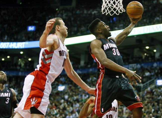 Nov 29, 2013; Toronto, Ontario, CAN; Miami Heat guard Norris Cole (30) goes to pass the ball back as Toronto Raptors forward Steve Novak (16) defends at the Air Canada Centre. Miami defeated Toronto 90-83. Mandatory Credit: John E. Sokolowski-USA TODAY Sports