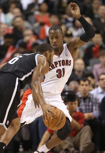 Nov 26, 2013; Toronto, Ontario, CAN; Toronto Raptors guard Terrence Ross (31) defends against Brooklyn Nets forward Alan Anderson (6) at Air Canada Centre. The Nets beat the Raptors 102-100. Mandatory Credit: Tom Szczerbowski-USA TODAY Sports