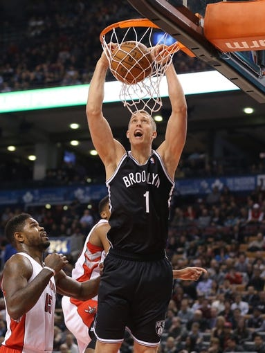 Nov 26, 2013; Toronto, Ontario, CAN; Brooklyn Nets forward Mason Plumlee (1) dunks as Toronto Raptors forward Amir Johnson (15) tries to defend at Air Canada Centre. The Nets beat the Raptors 102-100. Mandatory Credit: Tom Szczerbowski-USA TODAY Sports