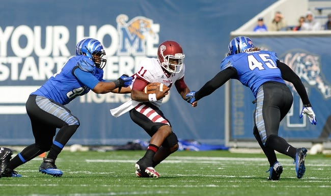 Nov 30, 2013; Memphis, TN, USA; Temple Owls quarterback P.J. Walker (11) carries the ball against Memphis Tigers linebacker Anthony Brown (45) and Memphis Tigers defensive lineman Corey Jones (94) during the first quarter at Liberty Bowl Memorial. Mandatory Credit: Justin Ford-USA TODAY Sports