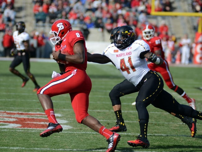 Nov 30, 2013; Raleigh, NC, USA; North Carolina State Wolfpack quarterback Brandon Mitchell (8) runs the ball as he is pursued by Maryland Terrapins linebacker Marcus Whitfield (41) during the first half at Carter Finley Stadium. Mandatory Credit: Rob Kinnan-USA TODAY Sports