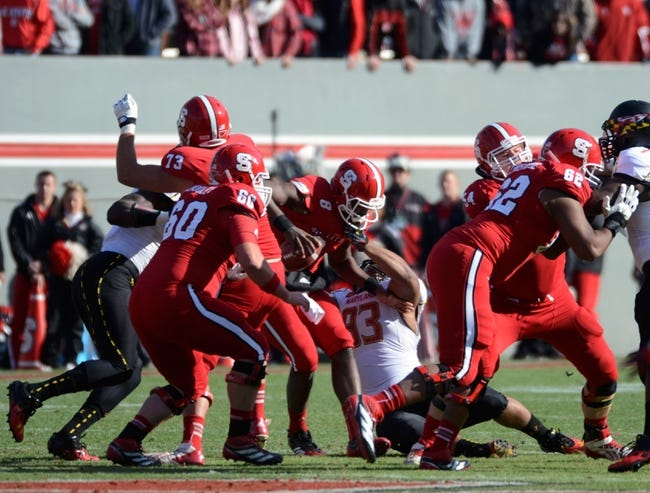 Nov 30, 2013; Raleigh, NC, USA; North Carolina State Wolfpack quarterback Brandon Mitchell (8) is sacked by Maryland Terrapins defensive lineman Andre Monroe (93) during the first half at Carter Finley Stadium. Mandatory Credit: Rob Kinnan-USA TODAY Sports
