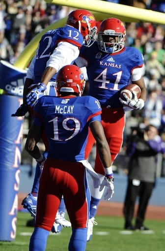 Nov 30, 2013; Lawrence, KS, USA; Kansas Jayhawks tight end Jimmay Mundine (41) celebrates a touchdown with wide receiver Christian Matthews (12) against the Kansas State Wildcats in the first half at Memorial Stadium. Mandatory Credit: John Rieger-USA TODAY Sports