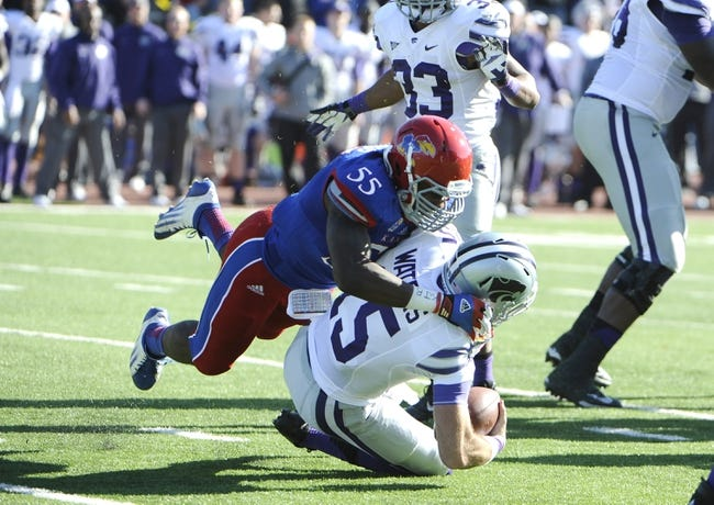 Nov 30, 2013; Lawrence, KS, USA; Kansas State Wildcats quarterback Jake Waters (15) is sacked by Kansas Jayhawks linebacker Michael Reynolds (55) in the first half at Memorial Stadium. Mandatory Credit: John Rieger-USA TODAY Sports