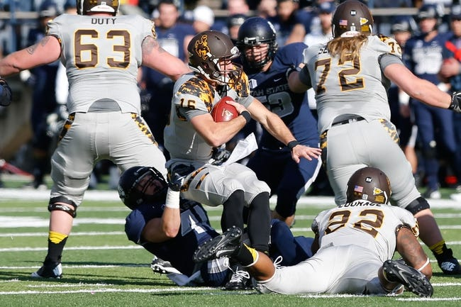 Nov 30, 2013; Logan, UT, USA; Wyoming Cowboys quarterback Brett Smith (16) is sacked by Utah State Aggies linebacker Nick Vigil (41) during the first quarter at Romney Stadium. Mandatory Credit: Chris Nicoll-USA TODAY Sports