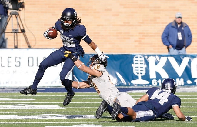 Nov 30, 2013; Logan, UT, USA; Utah State Aggies running back Kennedy Williams (30) tries to get away from Wyoming Cowboys safety Xavier Lewis (18) during the first quarter at Romney Stadium. Mandatory Credit: Chris Nicoll-USA TODAY Sports