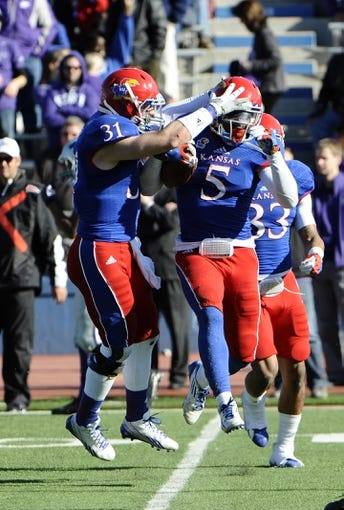 Nov 30, 2013; Lawrence, KS, USA; Kansas Jayhawks safety Isaiah Johnson (5) is congratulated by linebacker Ben Heeney (31) after intercepting a pass against the Kansas State Wildcats in the second half at Memorial Stadium. Kansas State won the game 31-10. Mandatory Credit: John Rieger-USA TODAY Sports