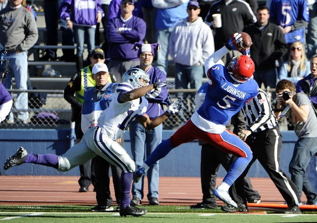 Nov 30, 2013; Lawrence, KS, USA; Kansas Jayhawks safety Isaiah Johnson (5) intercepts a pass intended for Kansas State Wildcats wide receiver Tyler Lockett (16) in the second half at Memorial Stadium. Kansas State won the game 31-10. Mandatory Credit: John Rieger-USA TODAY Sports