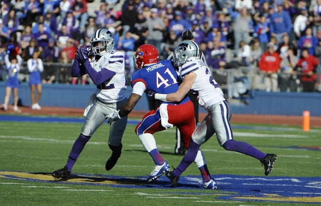 Nov 30, 2013; Lawrence, KS, USA; Kansas State Wildcats defensive back Dante Barnett (22) intercepts a pass intended for Kansas Jayhawks tight end Jimmay Mundine (41) while defended by defensive back Dylan Schellenberg (20) in the second half at Memorial Stadium. Kansas State won the game 31-10. Mandatory Credit: John Rieger-USA TODAY Sports