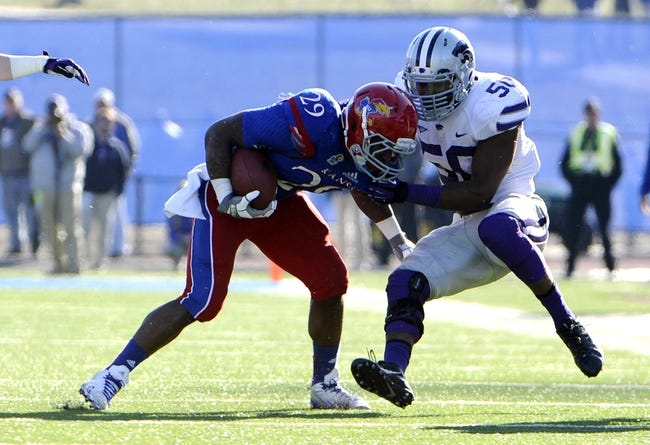 Nov 30, 2013; Lawrence, KS, USA; Kansas Jayhawks running back James Sims (29) is tackled by Kansas State Wildcats linebacker Tre Walker (50) in the second half at Memorial Stadium. Kansas State won the game 31-10. Mandatory Credit: John Rieger-USA TODAY Sports