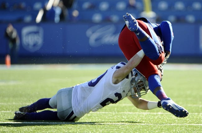 Nov 30, 2013; Lawrence, KS, USA; Kansas State Wildcats defensive back Dylan Schellenberg (20) tackles Kansas Jayhawks tight end Charles Brooks (86) in the second half at Memorial Stadium. Kansas State won the game 31-10. Mandatory Credit: John Rieger-USA TODAY Sports