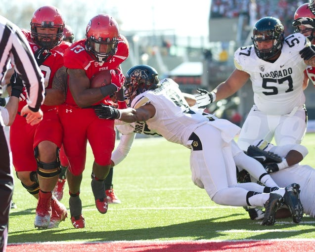 Nov 30, 2013; Salt Lake City, UT, USA; Utah Utes running back Kelvin York (13) breaks the tackle of Colorado Buffaloes defensive back Tedric Thompson (9) to score a touchdown during the first half at Rice-Eccles Stadium. Mandatory Credit: Russ Isabella-USA TODAY Sports