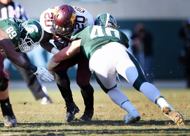 Nov 30, 2013; East Lansing, MI, USA; Minnesota Golden Gophers running back Donnell Kirkwood (20) is tackled by Michigan State Spartans linebacker Max Bullough (40) during the 2nd half a game at Spartan Stadium. MSU won 14-3.  Mandatory Credit: Mike Carter-USA TODAY Sports