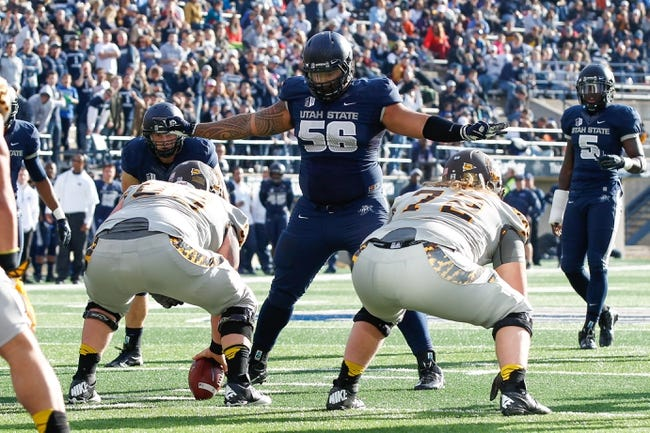 Nov 30, 2013; Logan, UT, USA; Utah State Aggies nose tackle AJ Pataiali'i (56) stands before the Wyoming Cowboys offensive line during the third quarter at Romney Stadium. Utah State Aggies won the game 35-7. Mandatory Credit: Chris Nicoll-USA TODAY Sports