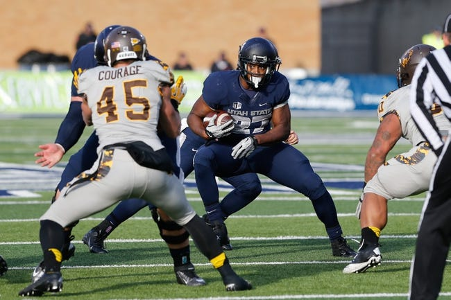Nov 30, 2013; Logan, UT, USA; Utah State Aggies running back Robert Marshall (27) runs up the field against the Wyoming Cowboys in the fourth quarter at Romney Stadium. Utah State Aggies won the game 35-7. Mandatory Credit: Chris Nicoll-USA TODAY Sports
