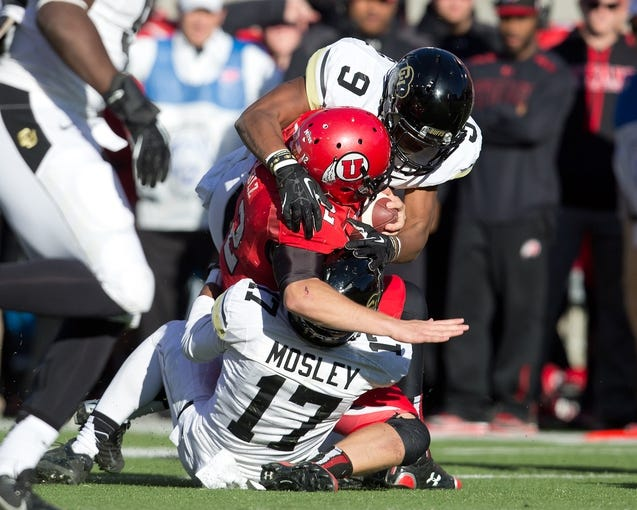Nov 30, 2013; Salt Lake City, UT, USA; Utah Utes quarterback Adam Schulz (12) is tackled by Colorado Buffaloes defensive backs Marques Mosley (17) and Tedric Thompson (9) during the second half at Rice-Eccles Stadium. Utah won 24-17. Mandatory Credit: Russ Isabella-USA TODAY Sports