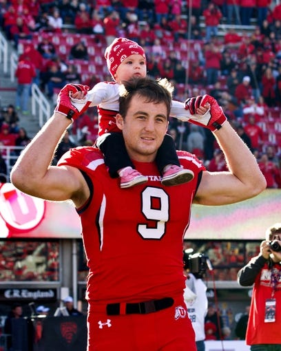 Nov 30, 2013; Salt Lake City, UT, USA; Utah Utes defensive end Trevor Reilly (9) carries his daughter Shayn on his shoulders as he is introduced for senior day prior to a game against the Colorado Buffaloes at Rice-Eccles Stadium. Utah won 24-17. Mandatory Credit: Russ Isabella-USA TODAY Sports