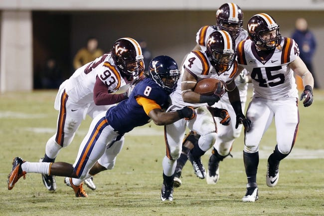 Nov 30, 2013; Charlottesville, VA, USA; Virginia Tech Hokies running back J.C. Coleman (4) carries the ball as Virginia Cavaliers safety Anthony Harris (8) attempts to tackle in the fourth quarter at Scott Stadium. The Hokies won 16-6. Mandatory Credit: Geoff Burke-USA TODAY Sports