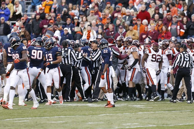 Nov 30, 2013; Charlottesville, VA, USA; Officials break up a fight between Virginia Cavaliers players and Virginia Tech Hokies players in the first quarter at Scott Stadium. The Hokies won 16-6. Mandatory Credit: Geoff Burke-USA TODAY Sports