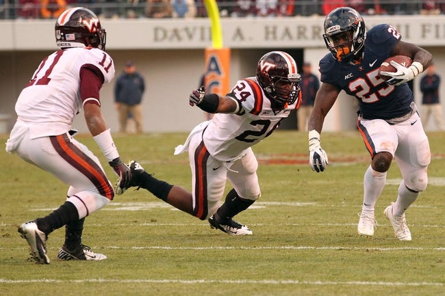 Nov 30, 2013; Charlottesville, VA, USA; Virginia Cavaliers running back Kevin Parks (25) carries the ball as Virginia Tech Hokies linebacker Tariq Edwards (24) attempts the tackle in the first quarter at Scott Stadium. The Hokies won 16-6. Mandatory Credit: Geoff Burke-USA TODAY Sports