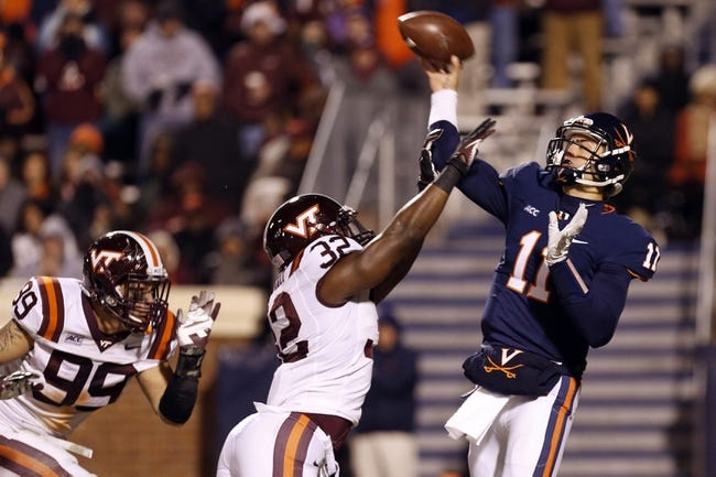 Nov 30, 2013; Charlottesville, VA, USA; Virginia Cavaliers quarterback Greyson Lambert (11) throws the ball as Virginia Tech Hokies linebacker Josh Trimble (32) defends in the third quarter at Scott Stadium. The Hokies won 16-6. Mandatory Credit: Geoff Burke-USA TODAY Sports