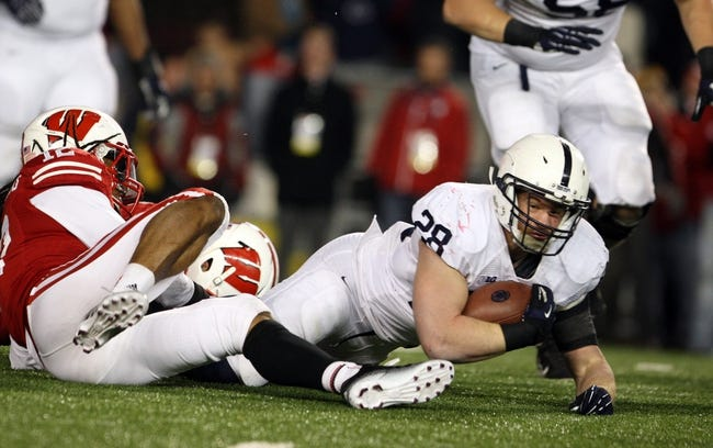 Nov 30, 2013; Madison, WI, USA; Penn State Nittany Lions running back Zach Zwinak stretches for extra yardage as Wisconsin Badgers safety Dezmen Southward (12) defends  at Camp Randall Stadium. Penn State defeated Wisconsin 31-24. Mandatory Credit: Mary Langenfeld-USA TODAY Sports