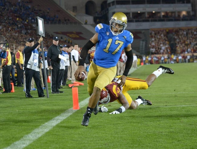 Nov 30, 2013; Los Angeles, CA, USA; UCLA Bruins quarterback Brett Hundley (17) eludes Southern California Trojans defensive end Leonard Williams (94) to score on a 4-yard touchdown run in the third quarter at Los Angeles Memorial Coliseum. Mandatory Credit: Kirby Lee-USA TODAY Sports