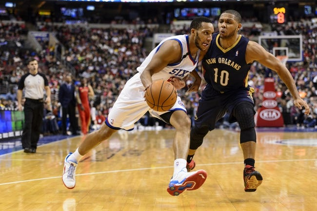 Nov 29, 2013; Philadelphia, PA, USA; Philadelphia 76ers guard Evan Turner (12) is defended by New Orleans Pelicans guard Eric Gordon (10) during the third quarter at the Wells Fargo Center. The Pelicans defeated the Sixers 121-105. Mandatory Credit: Howard Smith-USA TODAY Sports