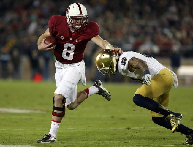 Nov 30, 2013; Stanford, CA, USA; Stanford Cardinal quarterback Kevin Hogan (8) holds off Notre Dame Fighting Irish safety Matthias Farley (41) for a tackle during the third quarter at Stanford Stadium. The Stanford Cardinal defeated the Notre Dame Fighting Irish 27-20. Mandatory Credit: Kelley L Cox-USA TODAY Sports
