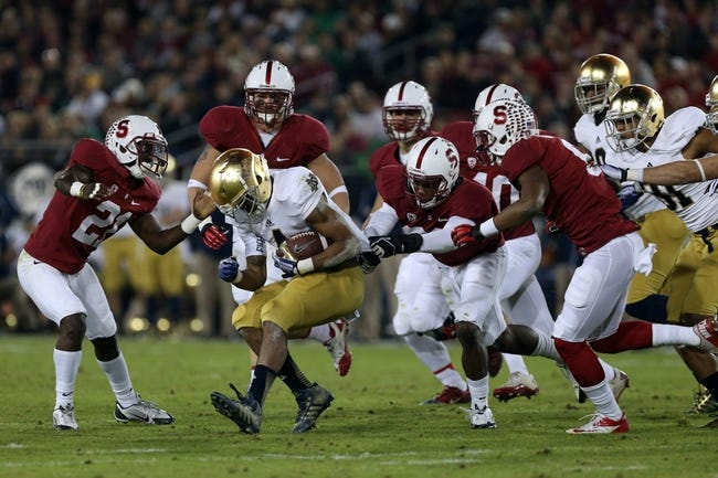 Nov 30, 2013; Stanford, CA, USA; Notre Dame Fighting Irish running back George Atkinson III (4) is brought down by Stanford Cardinal players on a kick off return during the third quarter at Stanford Stadium. The Stanford Cardinal defeated the Notre Dame Fighting Irish 27-20. Mandatory Credit: Kelley L Cox-USA TODAY Sports