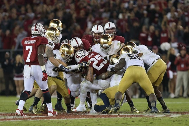 Nov 30, 2013; Stanford, CA, USA; Stanford Cardinal running back Tyler Gaffney (25) carries the ball against the Notre Dame Fighting Irish during the fourth quarter at Stanford Stadium. The Stanford Cardinal defeated the Notre Dame Fighting Irish 27-20. Mandatory Credit: Kelley L Cox-USA TODAY Sports