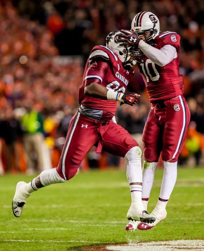 Nov 30, 2013; Columbia, SC, USA; South Carolina Gamecocks defensive end Chaz Sutton (90) celebrates with South Carolina Gamecocks linebacker Skai Moore (10) after Sutton recovered a fumble by the Clemson Tigers in the second half at Williams-Brice Stadium. Mandatory Credit: Jeff Blake-USA TODAY Sports