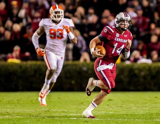 Nov 30, 2013; Columbia, SC, USA; South Carolina Gamecocks quarterback Connor Shaw (14) scrambles for a first down as Clemson Tigers defensive end Corey Crawford (93) pursues in the second quarter at Williams-Brice Stadium. Mandatory Credit: Jeff Blake-USA TODAY Sports